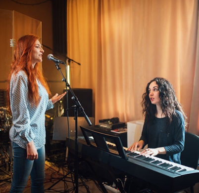 student girl sings in a vocal lesson to the accompaniment of a teacher on an electronic keyboard